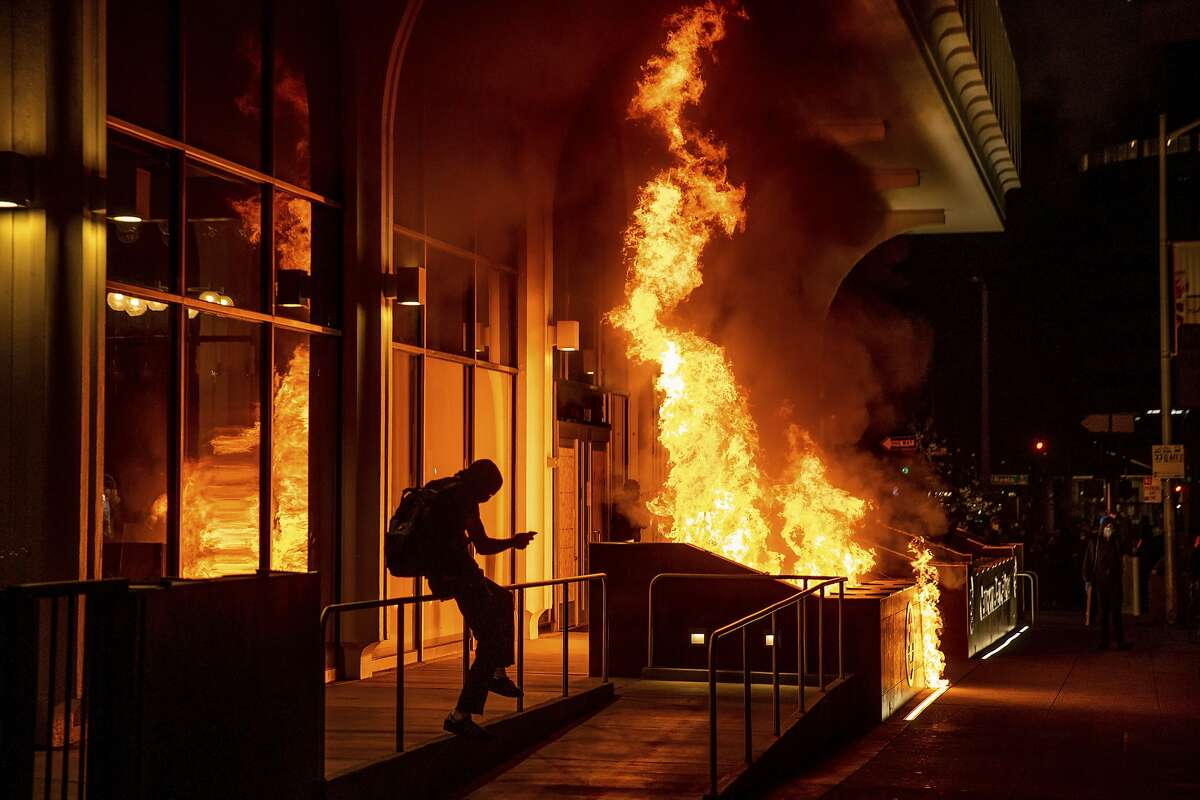 Demonstrators set fire to the front of the California Bank and Trust building during a protest against police brutality in Oakland, Calif., on Friday, April 16, 2021.