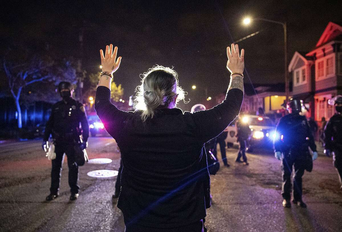 A demonstrator confronts a line of Oakland police officers during a protest against police brutality in Oakland, Calif., on Friday, April 16, 2021.