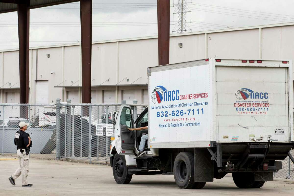 A U.S. Department of Homeland Security officer checks on a truck driver outside the National Association of Christian Churches facility, before allowing access to the facility where hundreds of migrant girls are being housed Monday, April 5, 2021 in Houston.