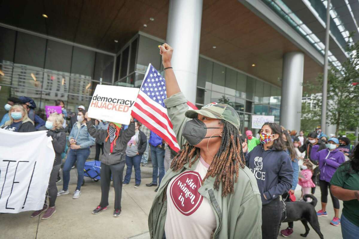 Tracy Daniel chants with other voters and activist organizations as they gathered at the Greater Houston Partnership building to demand the business group oppose the voter bills being considered by the Texas legislature Saturday, April 17, 2021, in Houston.