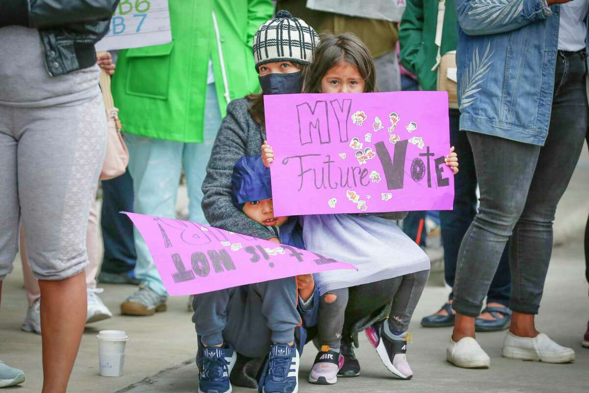 Diana Negreros (center) and her children Liam, 6 (left), and Nora, 4 (right), holds a sign with voters and activist organizations as they gather at the Greater Houston Partnership building to demand the business group oppose the voter bills being considered by the Texas legislature Saturday, April 17, 2021, in Houston.