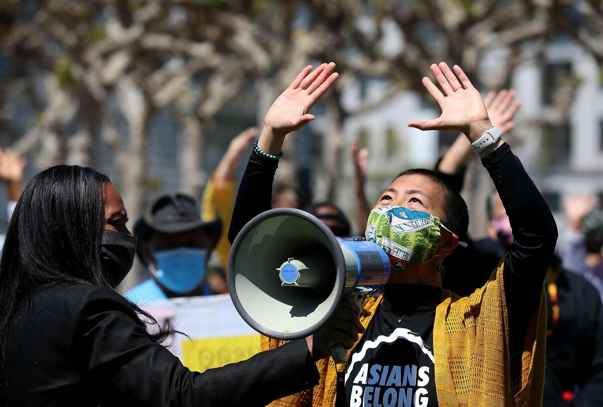 Sasanna Yee, a yoga teacher, leads a breathing exercise as Sheryl Davis, executive director of the Human Rights Commission holds a megaphone for her.