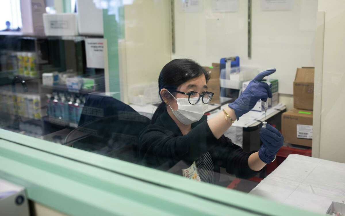 San Francisco General Hospital nurse Liezl Uy prepares Pfizer COVID-19 vaccines. The hospital rescued 1,000 doses of vaccine that were prematurely thawed in Humboldt County.