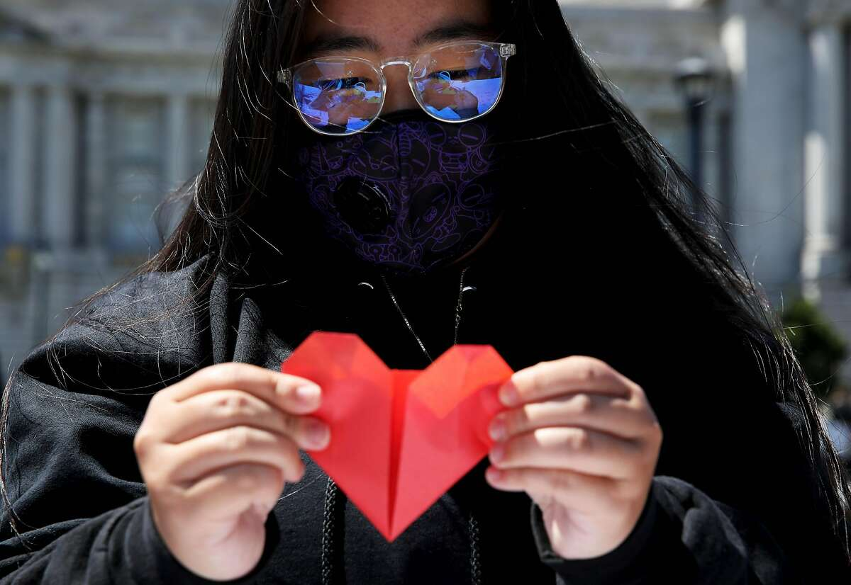 Jordyn Owyoung holds an origami heart during a unity event against anti-Asian violence at Civic Center Plaza, as part of the Campaign for Solidarity.