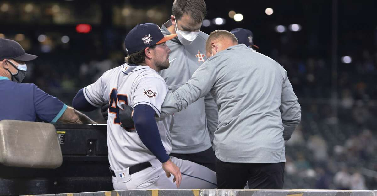 Houston Astros pitcher Blake Taylor is helped off the field following an injury during the eighth inning of the team's baseball game against the Seattle Mariners on Friday, April 16, 2021, in Seattle. (AP Photo/Jason Redmond)