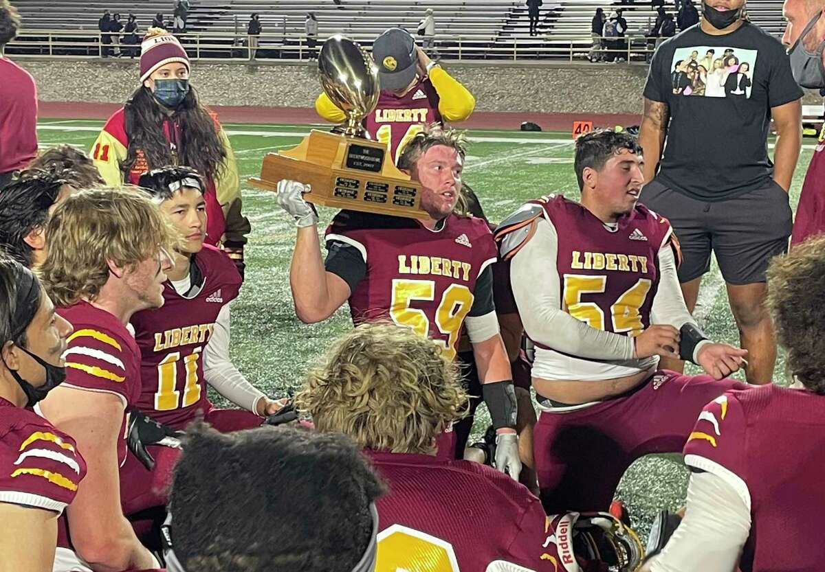 Liberty senior Jacob Tuttle holds the Brentwood Bowl Trophy on his shoulder as the team listens to postgame remarks from head coach Matt Hoefs.