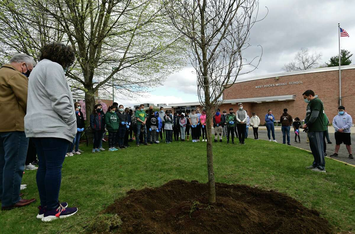 Students, faculty and parents commemorate with tree planting and a few words dedicated to a student who died last year, Ruth Israel at West Rocks School's annual Spring Cleanup Saturday, April 17, 2021, in Norwalk, Conn. The group of students, parents and teachers cleaned the school ground of trash followed by the tree planting.