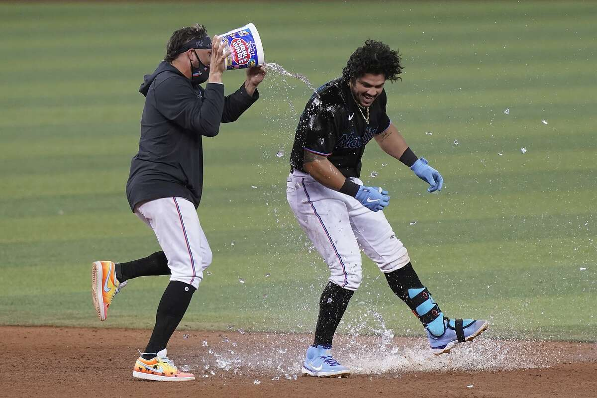 The Marlins' Miguel Rojas pours a bucket of water on Jorge Alfaro after Alfaro hit a double to drive in the winning run.