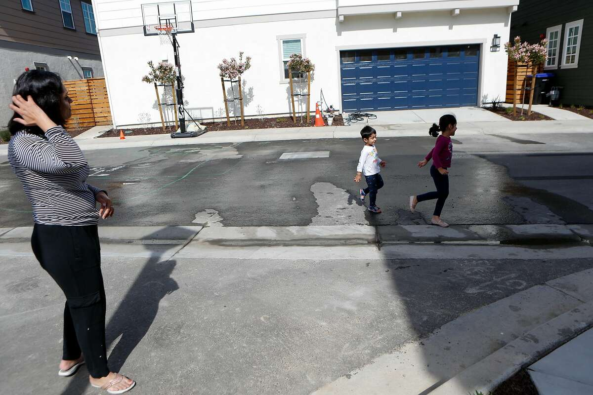 Shreya Yogi watches as her son Viaan and daughter Aria play outside their home.