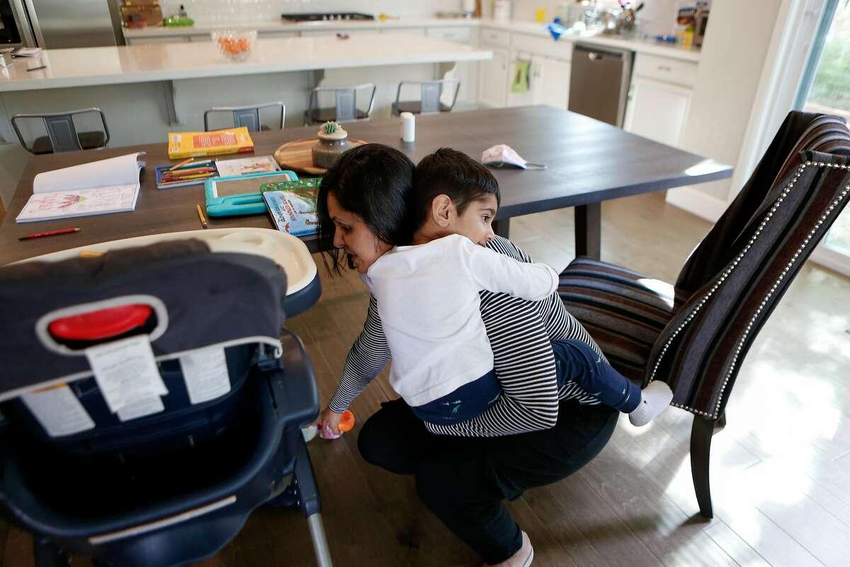 Shreya Yogi cleans up as she holds her son, Viaan, 2, in her Pleasanton home.