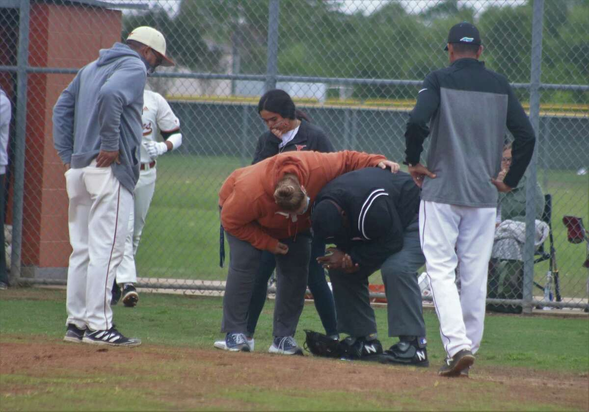 Dobie High School trainer Lori Mahon checks on home-plate umpire Folton Brown after a pitch skimmed off a Dobie batter and then hit Brown's left hand. The raw day only made the injury feel worse. But by the end of the contest, Brown said it was a fun game to umpire.