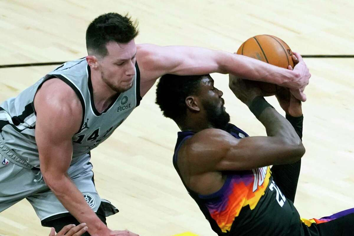 Spurs forward Drew Eubanks (14) blocks the shot of Phoenix Suns center Deandre Ayton during the second half of an NBA basketball game Saturday, April 17, 2021, in Phoenix.