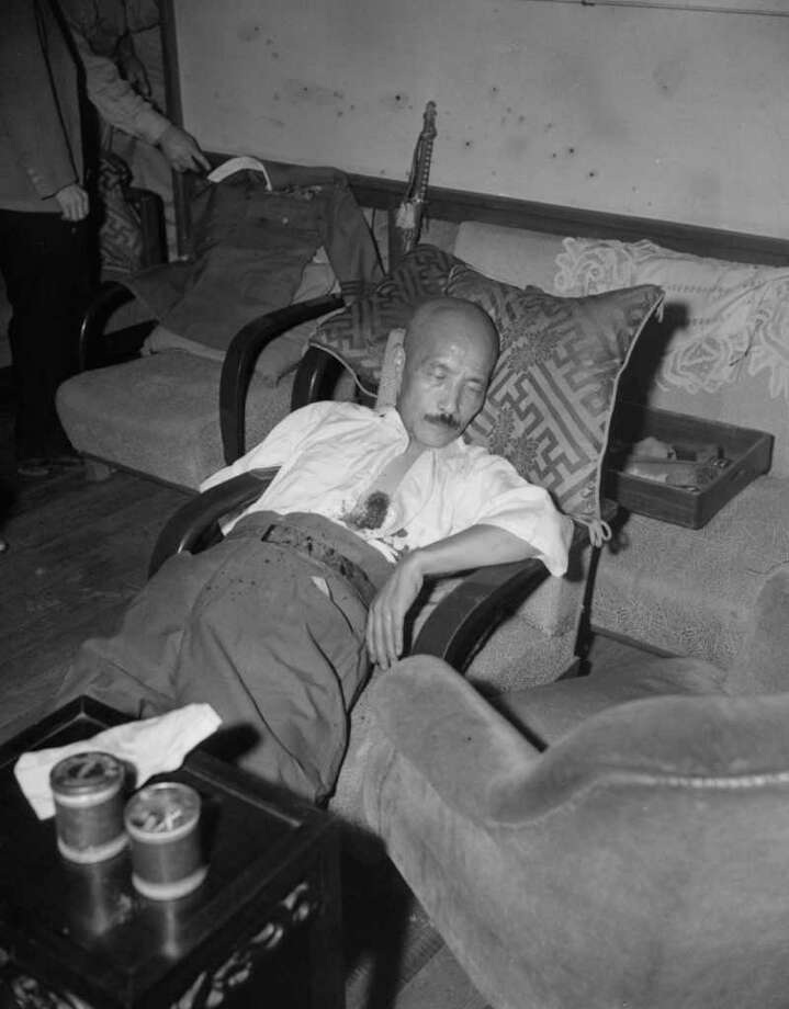 In this Sept. 11, 1945, file photo made in Tokyo, Gen. Hideki Tojo lies semiconscious in a chair with a gaping bullet wound just below the heart after a suicide attempt. Sixty-five years after the former Army intelligence officer prevented Tojo from successfully killing himself, John J. Wilpers Jr. is just beginning to speak publicly about his wartime experiences. (AP Photo/Charles Gorry, File) Photo: Charles Gorry / AP