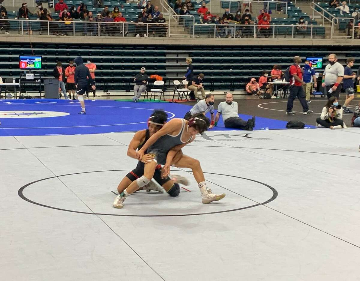 Katy's John Raymundo and Cinco Ranch's Esai Deras compete for the 106-pound championship at the Region III-6A tournament April 17 at Merrell Center.