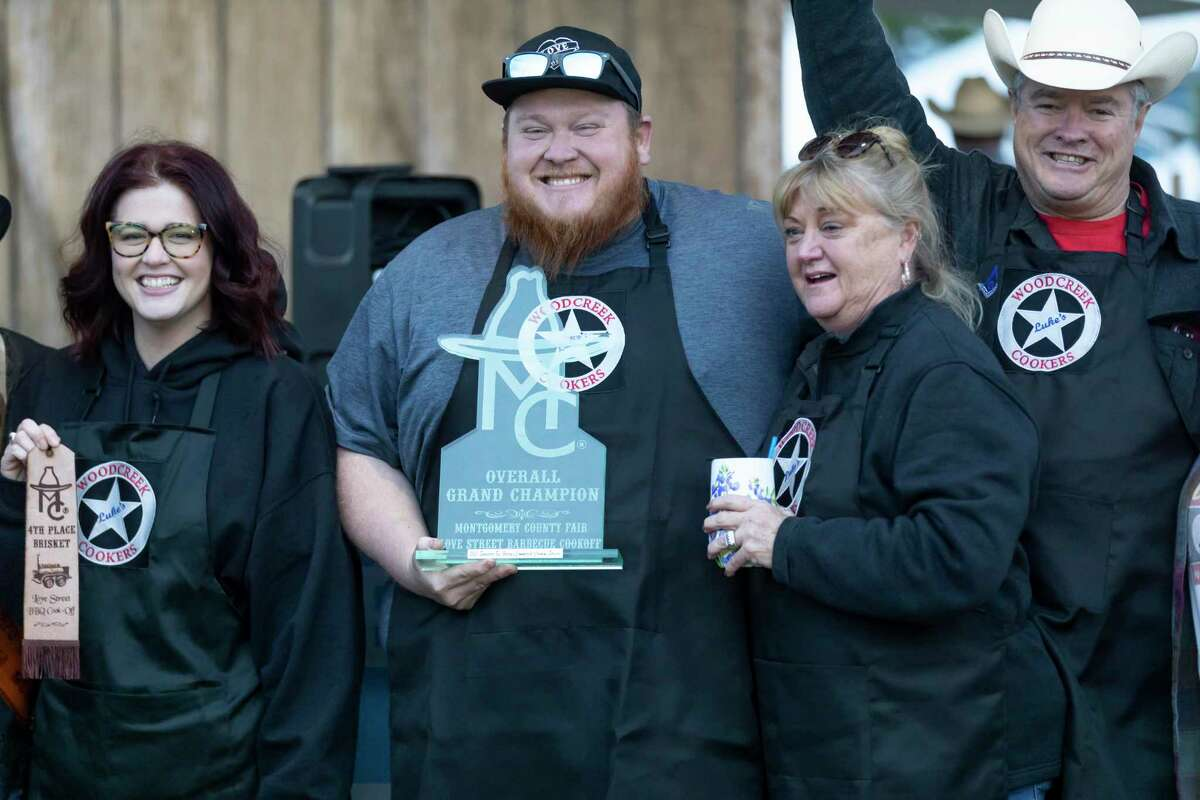 Jeremy McMinn, cook for Luke's Woodcreek Cookers, center, poses with his teammates after winning overall grand champion Saturday during the Midnight Love Street BBQ Cookoff awards ceremony at the Montgomery County Fair & in Conroe. This year an estimated 110 teams competed.