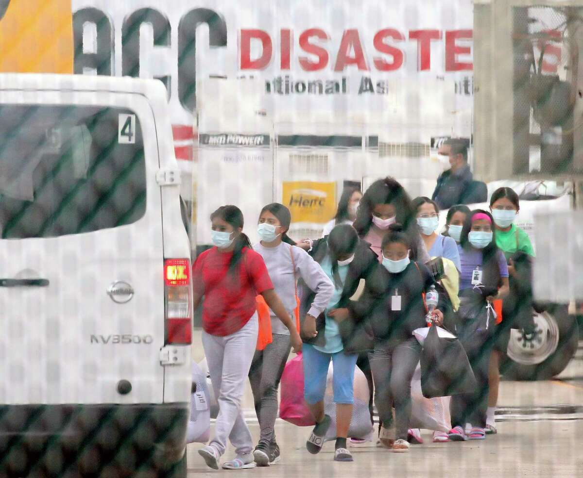 Teenage migrant girls are loaded into vans to be transported out of the National Association of Christian Churches facility, on Saturday, April 17, 2021, in Houston. A facility in Houston that housed girls who crossed U.S. border unaccompanied is being closed and the girls immediately moved, the U.S. Department of Health and Human Services said Saturday.(Godofredo A. Vásquez/Houston Chronicle via AP)