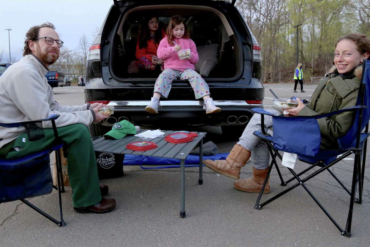 """The Dombrow family, of Westport, including from left Matt, Leah, 11, Alexa, 8, and Melissa, enjoy a tailgate at the Remarkable Theater's drive-in showing of """"Goonies"""" on Friday, April 16, 2021, in Westport, Conn."""