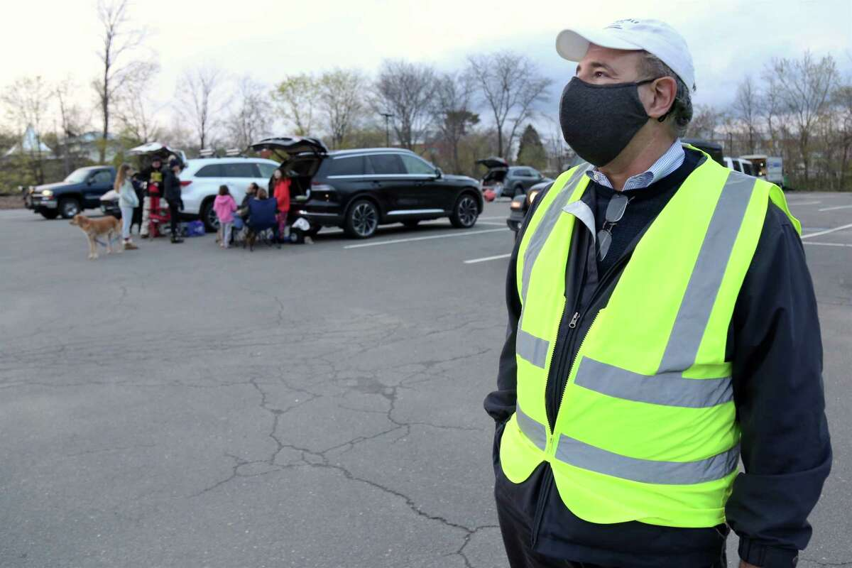 """State Rep. Jonathan Steinberg, who serves on the board, helps direct traffic at the Remarkable Theater's drive-in showing of """"Goonies"""" on Friday, April 16, 2021, in Westport, Conn."""