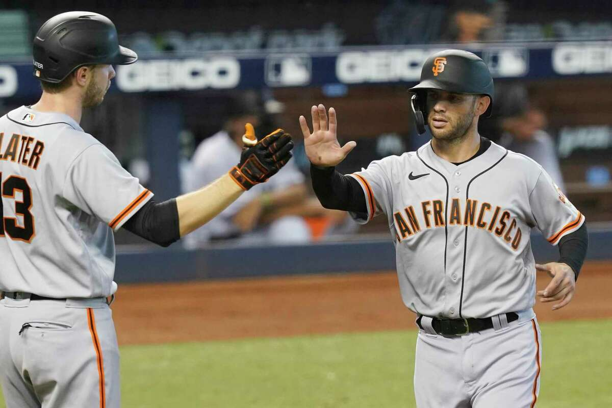 San Francisco Giants' Austin Slater (13) congratulates Tommy La Stella after he scores a run in the third inning of a baseball game against the Miami Marlins, Sunday, April 18, 2021, in Miami.