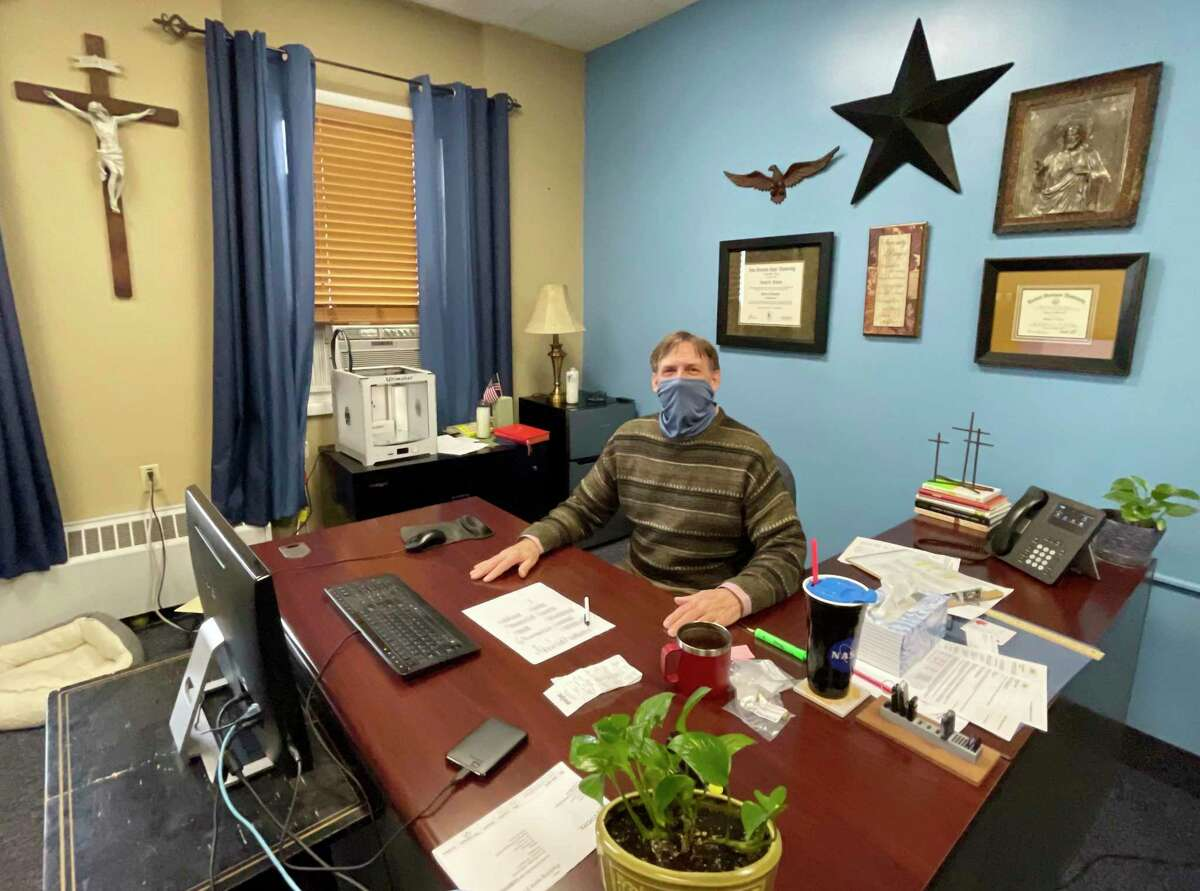 JB Watters, principal of St. Mary Catholic School in Big Rapids, shares a smile with the camera in his office during a recent school day. At the end of the school year, Watters will head out west, to Texas, for a new position. (Pioneer photo/Bradley Massman)