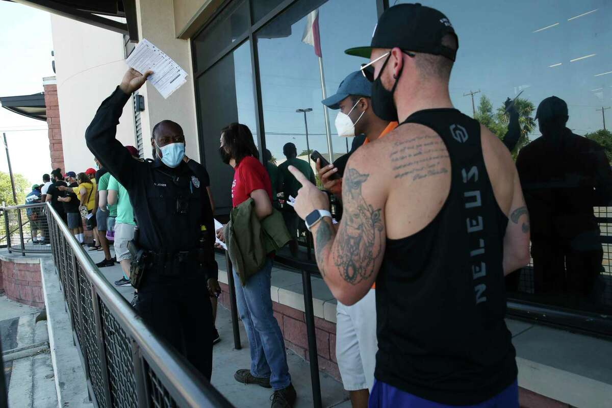 Bexar County Sheriff's Deputy E. Jones hands out voter registration forms outside the Bexar County Elections Department last Oct. 5.