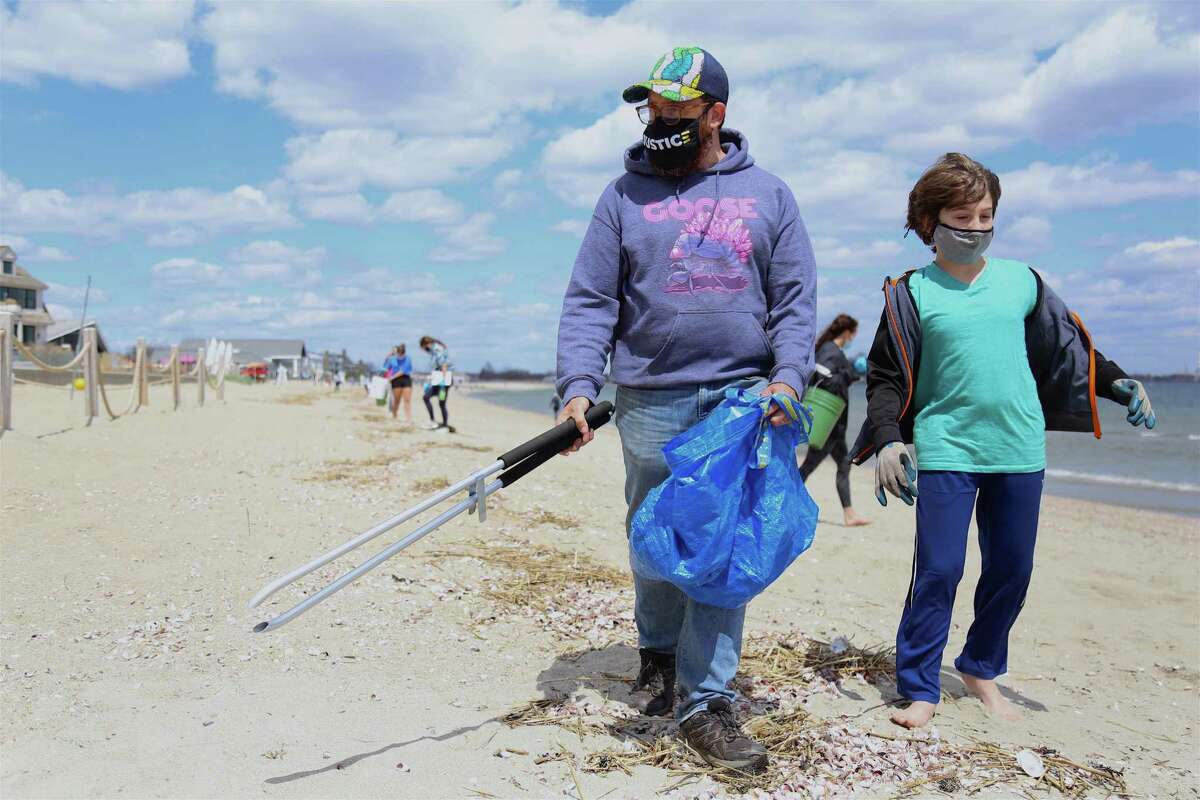 Brad Kerner, of Fairfield, a.k.a. The Eco Dude, and his son Jonah, 11, pitch in at the cleanup at Penfield Beach on Sunday, April 18, 2021, in Fairfield, Conn.