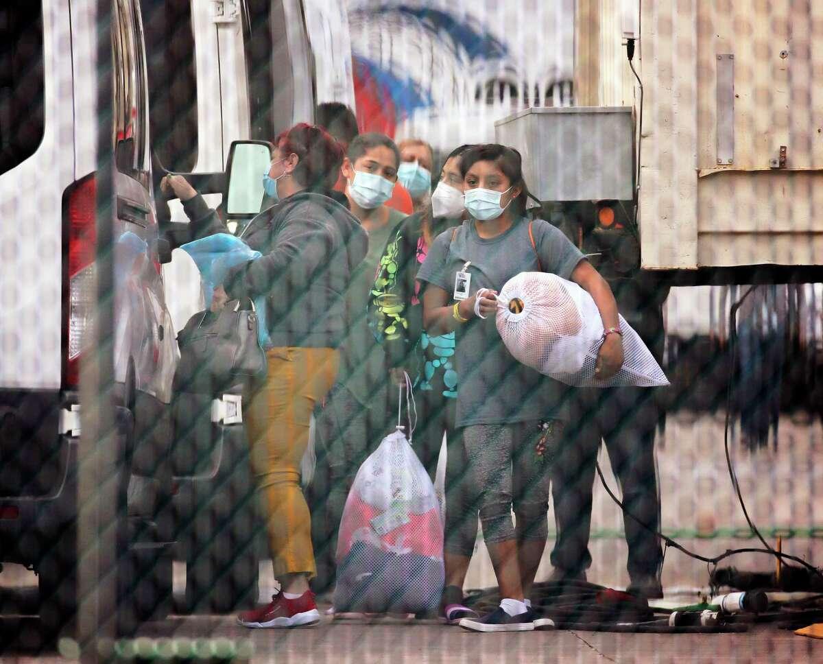 Niñas adolescentes migrantes son subidas a vehículos para retirarlas de un centro de la Asociación Nacional de Iglesias Cristianas que está siendo cerrado en Houston, el sábado 17 de abril de 2021.