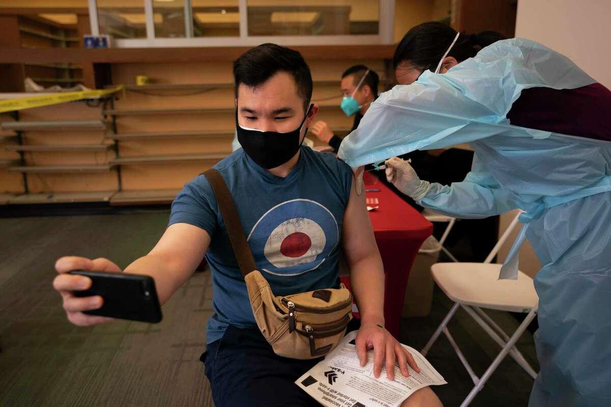 Fotografía de archivo del 12 de abril de 2021 de Freeson Wong, de 31 años, tomándose una selfie mientras recibe una dosis de la vacuna de Moderna contra el coronavirus en el barrio Chinatown de Los Ángeles.