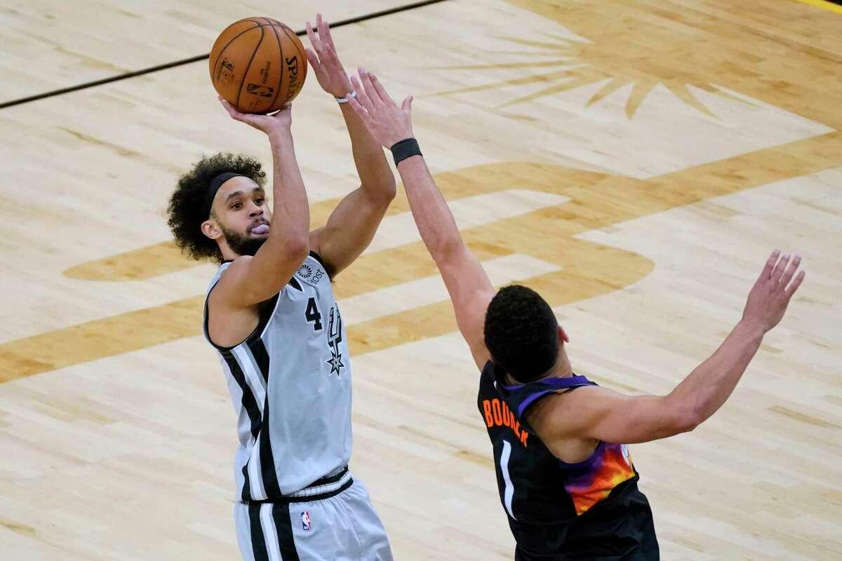 San Antonio Spurs guard Derrick White shoots over Phoenix Suns guard Devin Booker (1) during the first half of an NBA basketball game Saturday, April 17, 2021, in Phoenix. (AP Photo/Rick Scuteri)