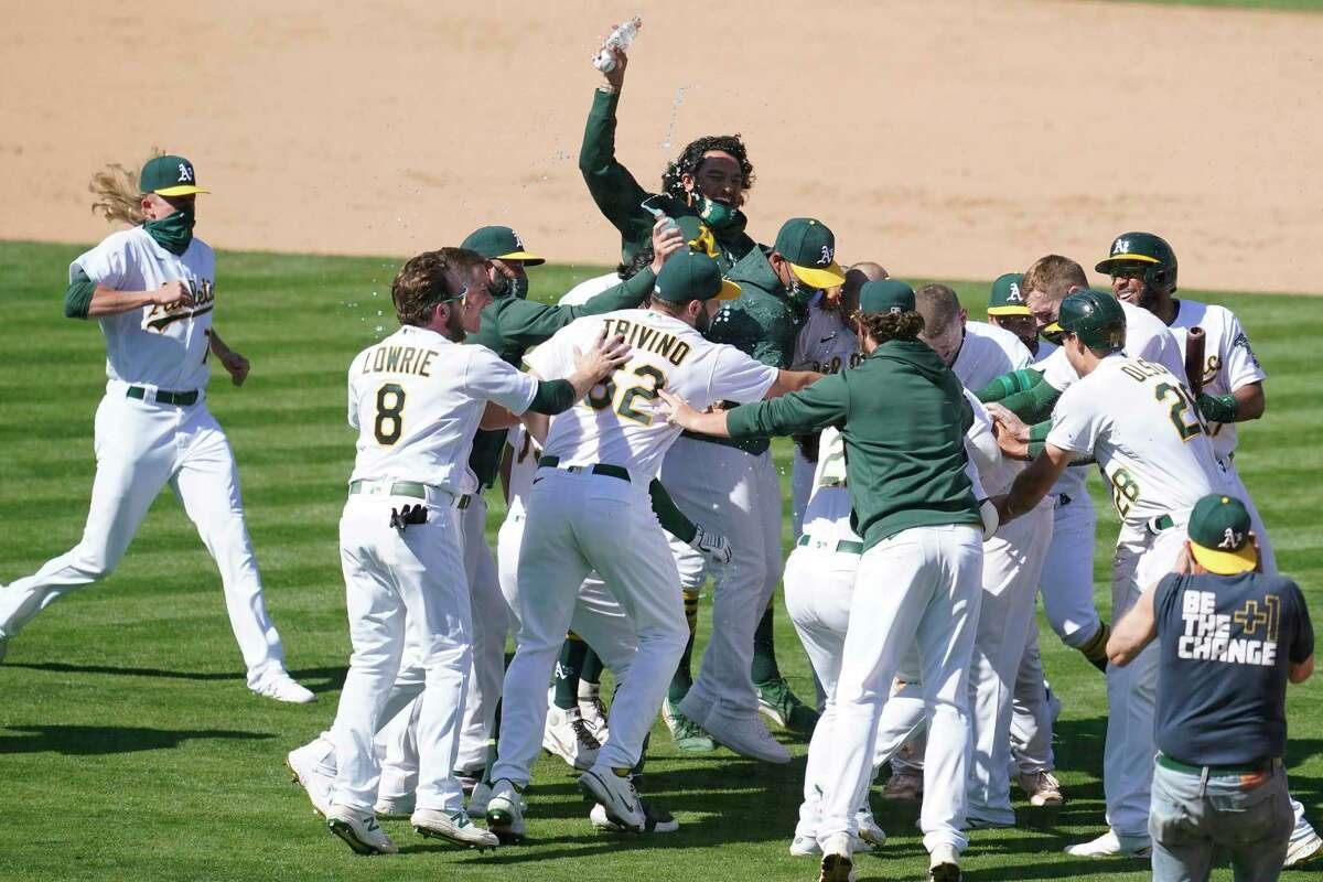 The A's Mitch Moreland is the center of attention after his ninth-inning grounder led to the winning run scoring.