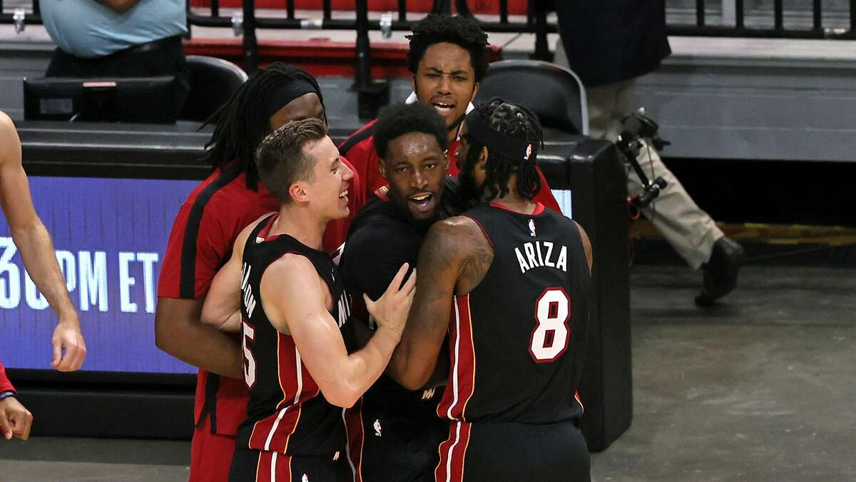 Miami Heat center Bam Adebayo (13) celebrates with teammates after hitting the winning shot over Brooklyn Nets forward Jeff Green (8) in the fourth quarter at the AmericanAirlines Arena on Sunday, April 18, 2021 in Miami, Florida. (David Santiago/Miami Herald/TNS)