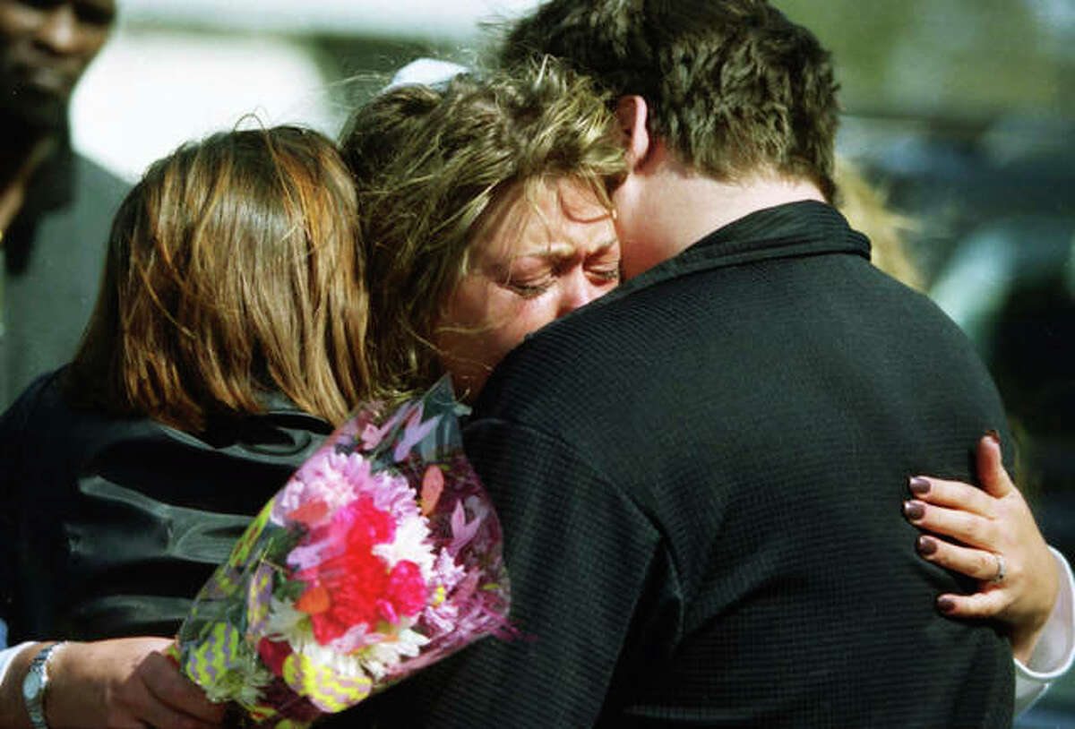 People hug on April 15, 2001, the day after the call came into the Elgin Police Department to respond to what would now be called a mass shooting.