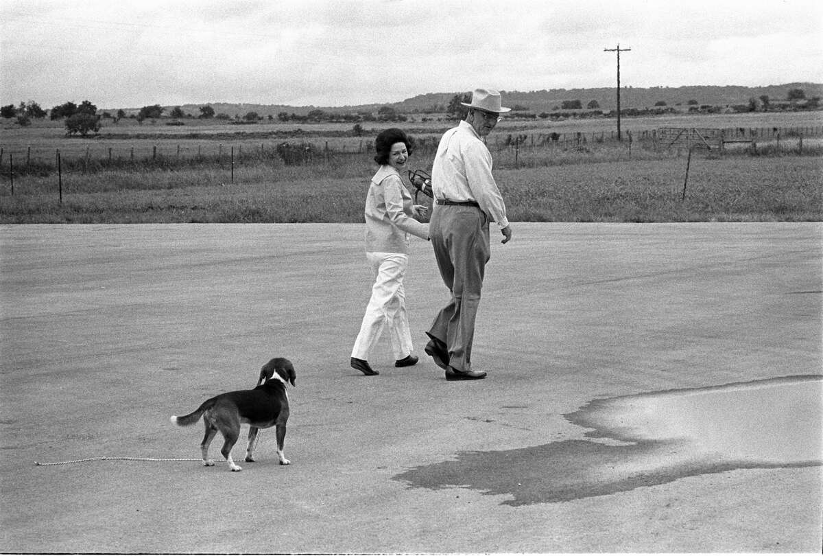 This May 1965 image released by the LBJ Library shows President Lyndon B. Johnson and Lady Bird on the LBJ Ranch near Stonewall, Texas, with one of their beagles.