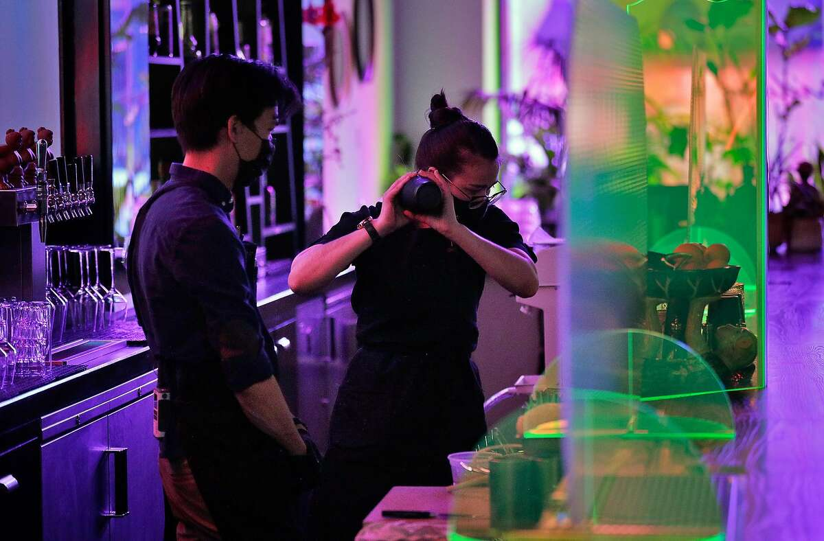 Owner William Tsui works with new bartender Julie Kunz at Viridian in Oakland. Tsui said it was challenging hiring enough people to reopen for indoor dining.