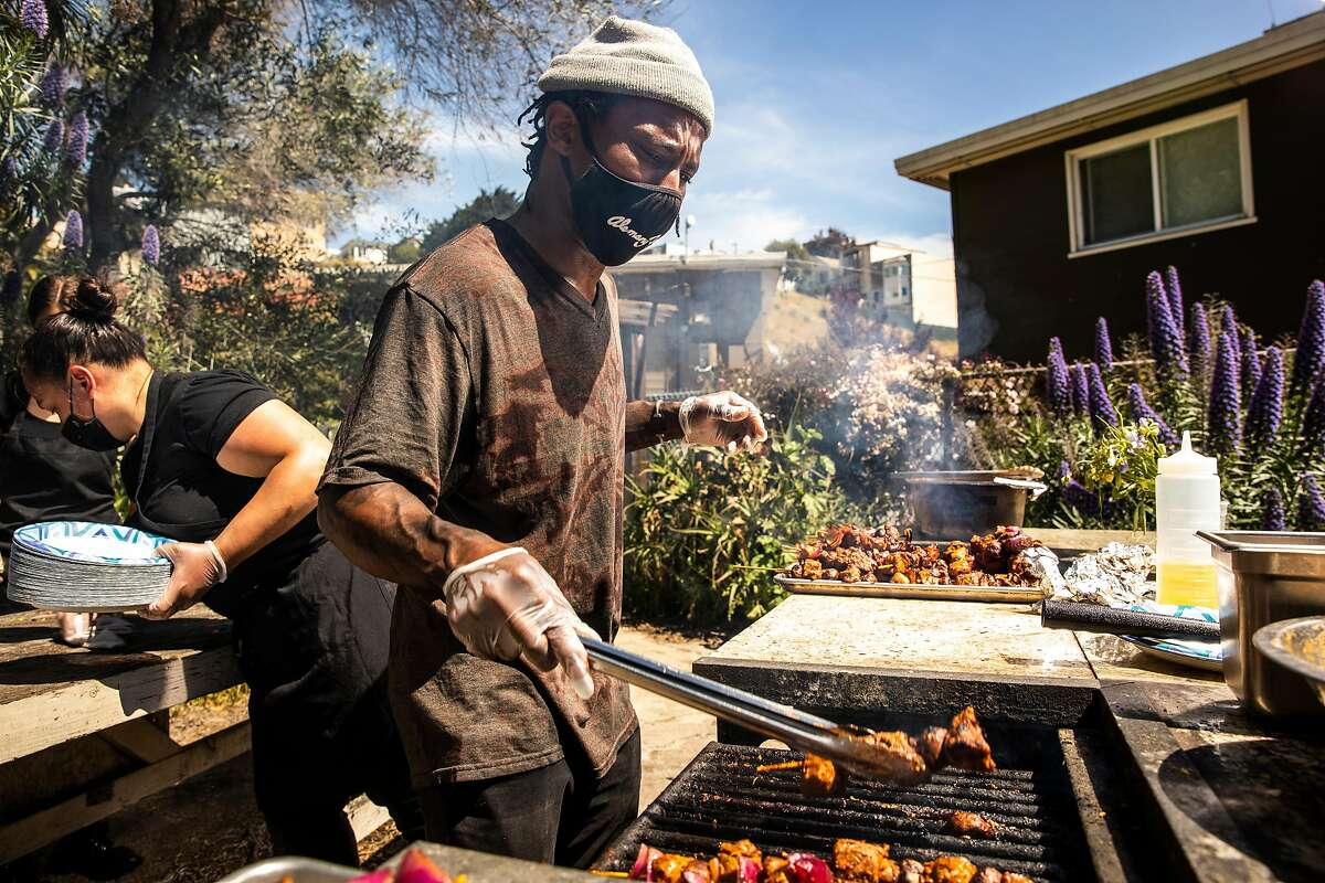 Christopher Renfro, co-founder of Two Eighty Project, grills food for a Feed the People Collective event.  The kitchen is next to the Alemany Farm where he grows vines.