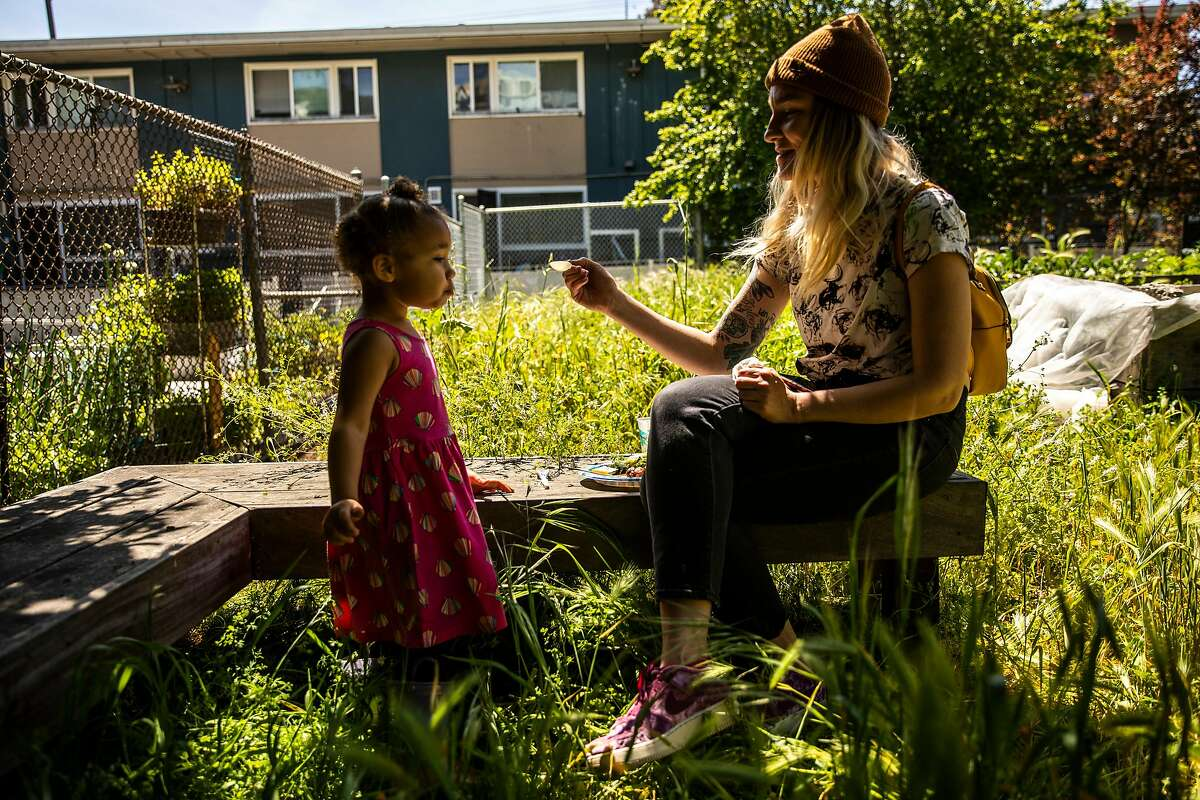 Jannea Tschirch, co-founder of Eighty Project, feeds daughter Ahmarie Renfro next to the Alemany Farm.