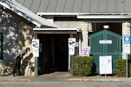 An election official waits for voters at the entrance to the Lions Field poll site on Broadway early on election day, Tuesday, Nov. 3, 2020. There were few voters; as most had taken advantage of early voting.