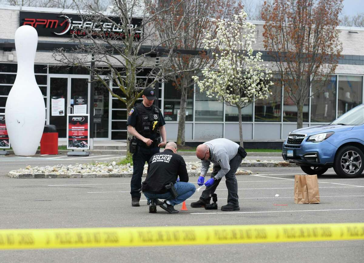 Investigators survey the scene of a fatal shooting in the parking lot of RPM Raceway in Stamford, Conn. Monday, April 19, 2021. A 19-year-old Stamford man was fatally shot after a get-together with fellow car enthusiasts went south Sunday night, according to police.