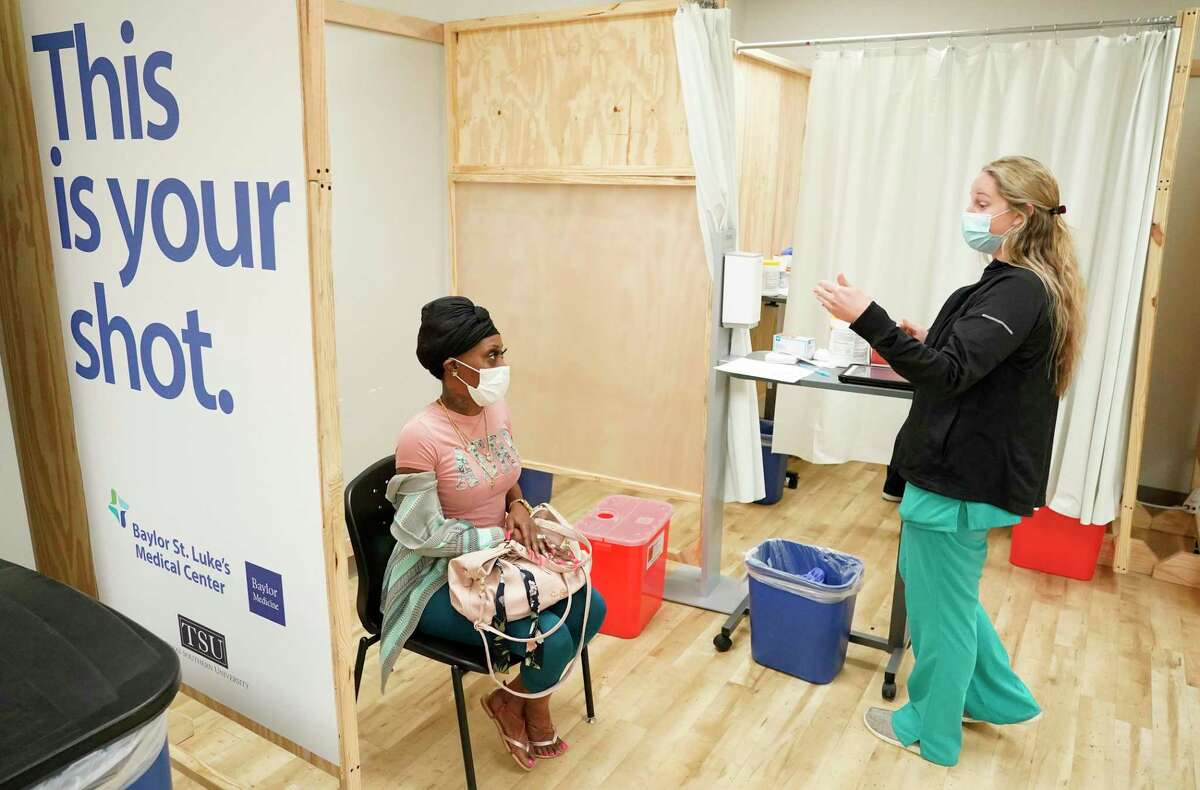 Demetria Caston awaits a Pfizer COVID-19 vaccination from registered nurse Kayla Shepherd at the St. Luke's Health walk-in vaccination clinic at Texas Southern University in Houston on Monday. St. Luke's could offer a second such clinic next week.