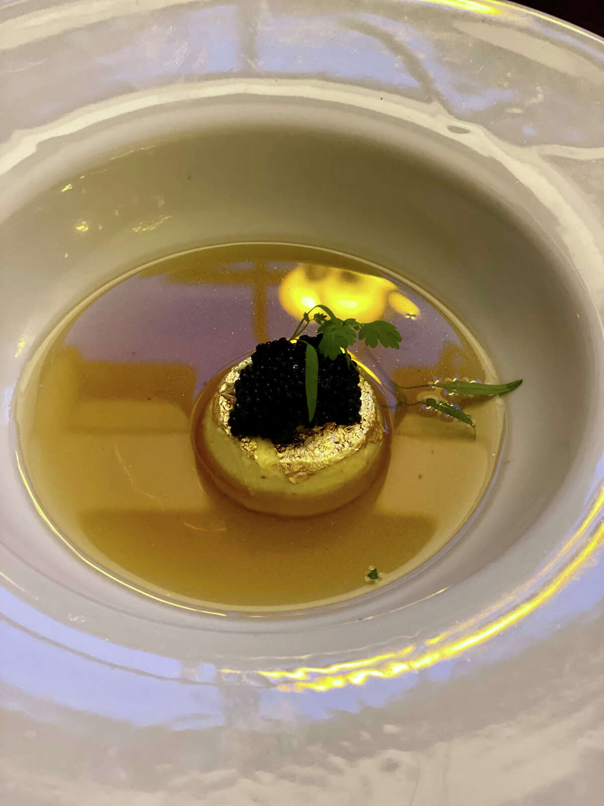 Edible gold foil wraps a savory custard that is topped with caviar and bathed in crystal-clear bison consommé at Jack's Oyster House in Albany.