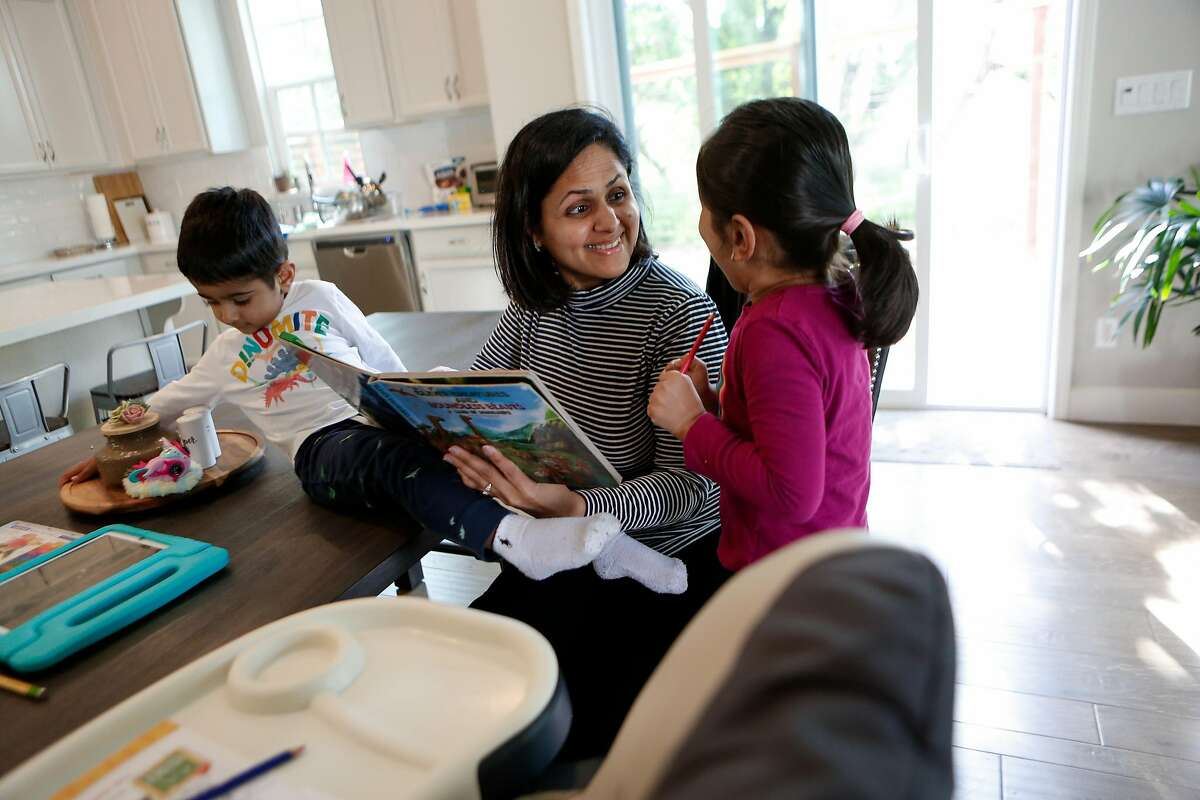 Shreya Yogi, who lost her job twice during the pandemic, reads to her children Viaan (left) and Aria in their home in Pleasanton.