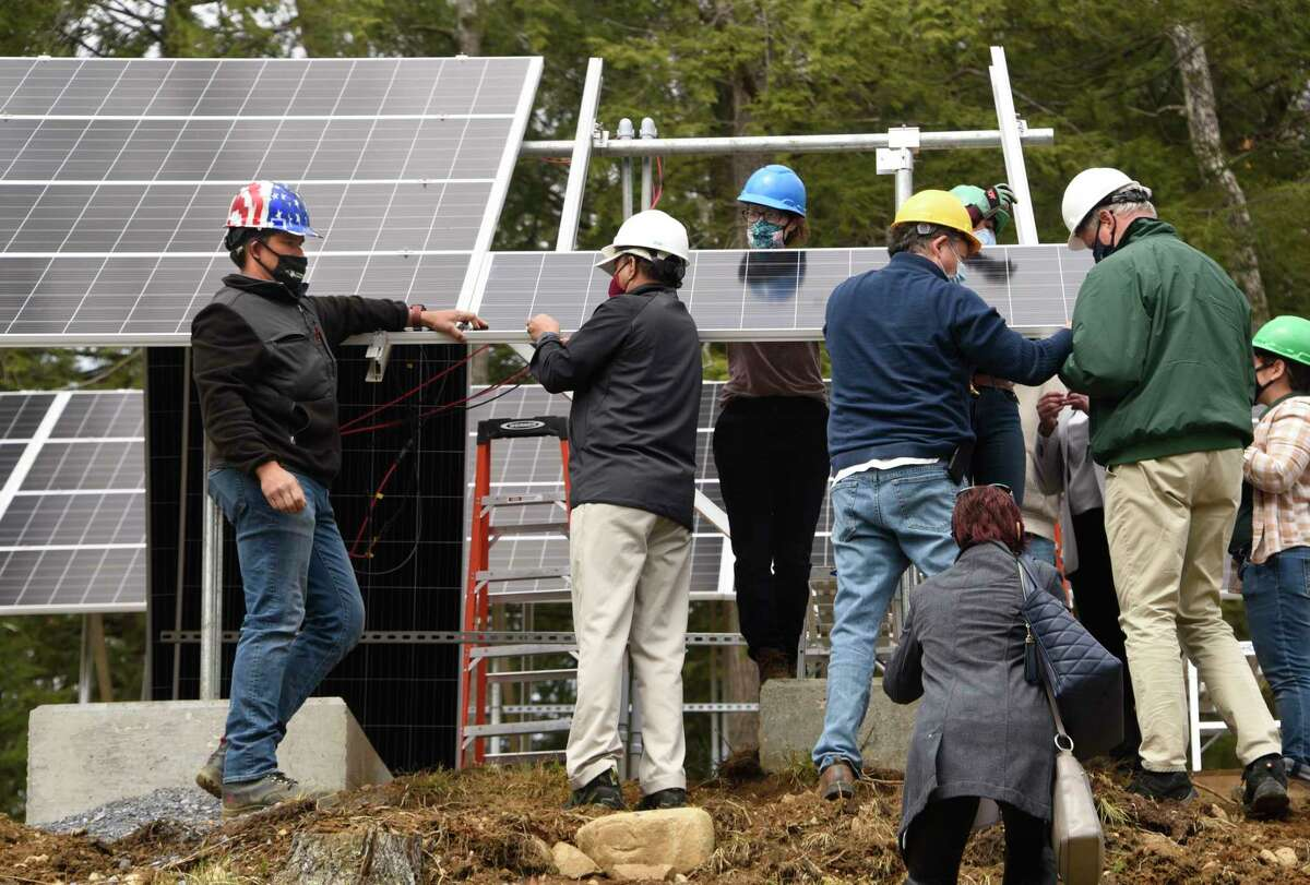 Erik Kulleseid, commissioner of New York State Office of Parks, Recreation and Historic Preservation, right, helps install one of the last solar panels at Grant Cottage State Historic Site during a press conference on new technology for parks on Monday, April 19, 2021 in Wilton, N.Y. Grant Cottage is the first NYS park to disconnect from the grid. (Lori Van Buren/Times Union)