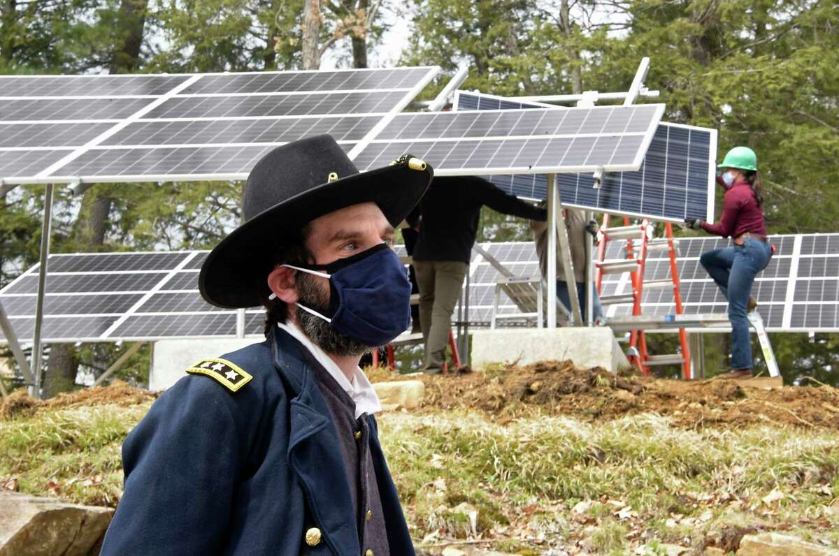 Operations Manager at Grant Cottage State Historic Site Ben Kemp, dressed as Ulysses S. Grant, talks to people as workers from New York State Parks, Recreation and Historic Preservation install solar panels at Grant Cottage State Historic Site on Monday, April 19, 2021 in Wilton, N.Y. Grant Cottage is the first NYS park to disconnect from the grid. (Lori Van Buren/Times Union)