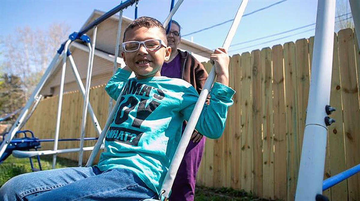 Braxton Lear, 5, and his mother, Shannon Lear, play on a swing at a relative's house in Caseyville.