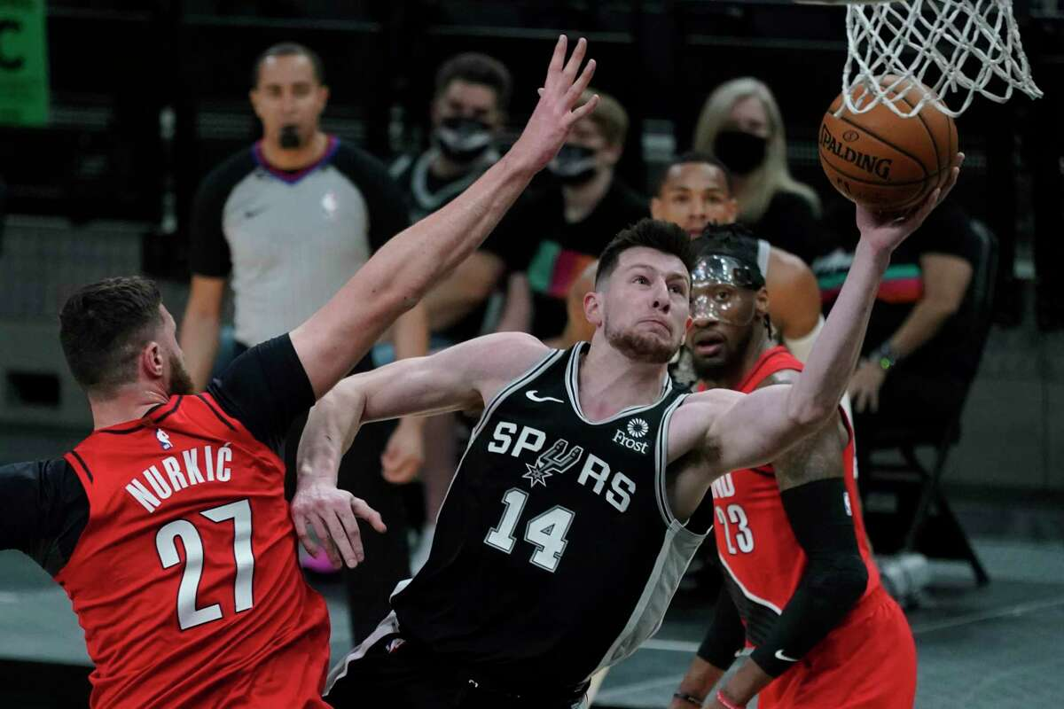 Spurs forward Drew Eubanks (14) drives to the basket past Portland Trail Blazers center Jusuf Nurkic (27) during the first half of an NBA basketball game in San Antonio, Friday, April 16, 2021.