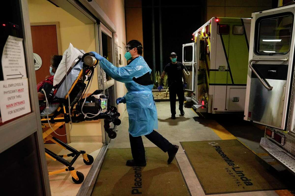 Emergency medical technician Thomas Hoang pushes a gurney into an emergency room to drop off a COVID-19 patient in Placentia (Orange County) on Jan. 8.