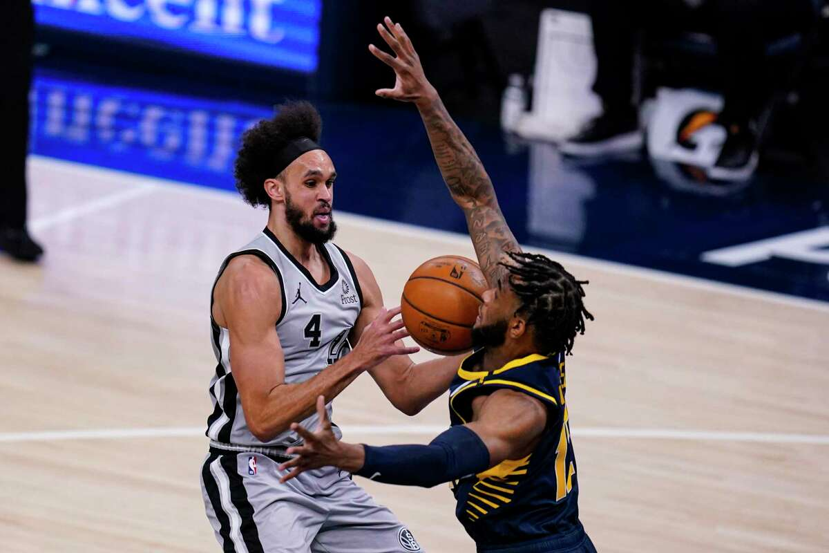 Spurs guard Derrick White (4) drives around Pacers forward Oshae Brissett (12) during the second half of an NBA basketball game in Indianapolis, Monday, April 19, 2021.