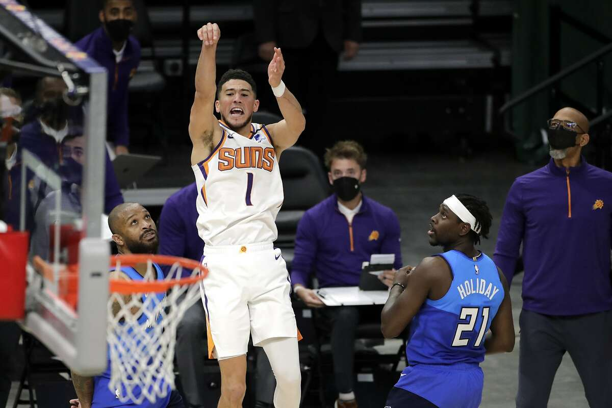 Devin Booker was fouled by P.J. Tucker (left) in the final second of overtime before making the winning free throw.