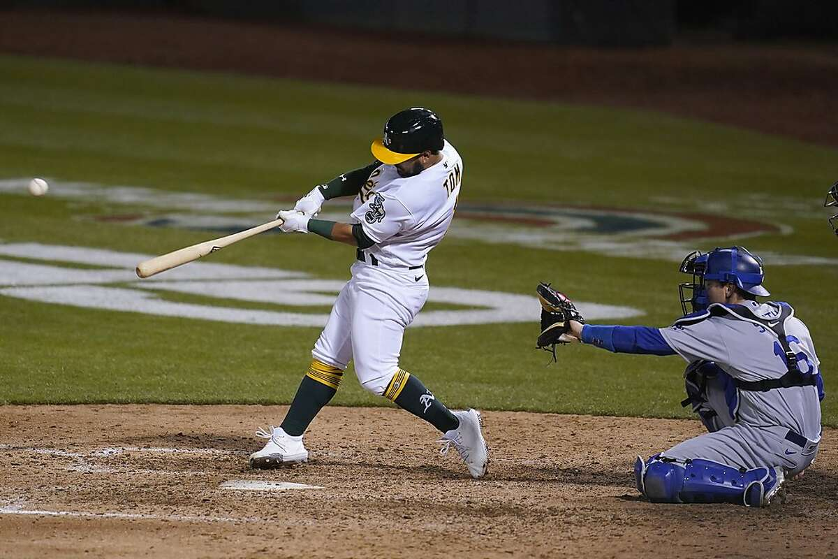 Oakland Athletics' Ka'ai Tom, left, hits a single in front of Los Angeles Dodgers catcher Will Smith during the eighth inning of a baseball game in Oakland, Calif., Monday, April 5, 2021. (AP Photo/Jeff Chiu)