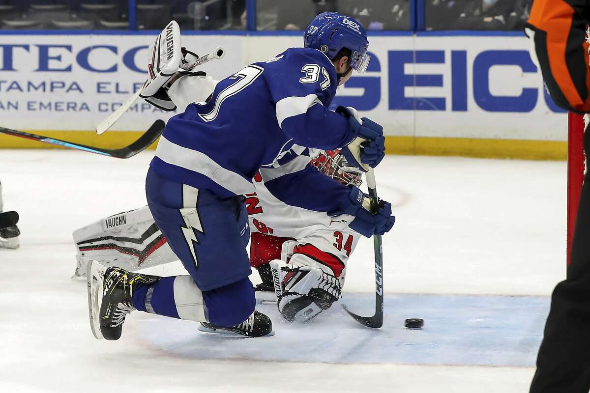 Tampa Bay Lightning's Yanni Gourde (37) scores the winning goal past Carolina Hurricanes goaltender Petr Mrazek, of the Czech Republic, during the overtime period of an NHL hockey game Monday, April 19, 2021, in Tampa, Fla. (AP Photo/Mike Carlson)